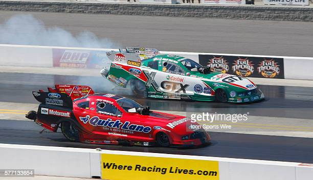 Ashley Force Hood smokes her tires along side of Bob Tasca III during Sunday Elimination rounds for the O'Reilly Auto Parts NHRA Nationals at the...