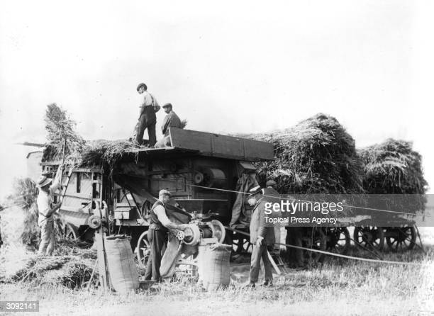 Farm workers grinding and threshing by motor at the Dennis Brothers' Farm in Kirton Lincolnshire