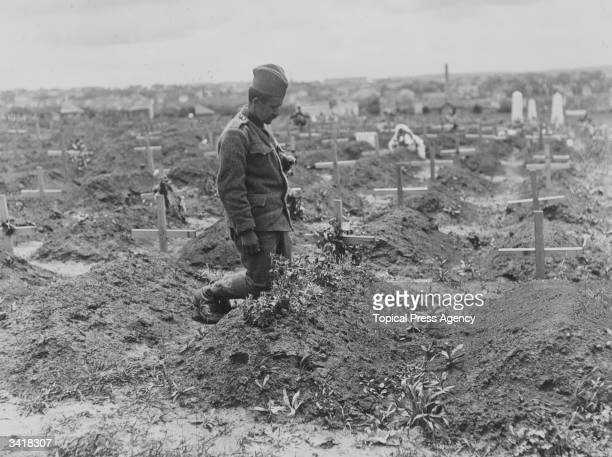 A Serbian soldier visits the grave of one of his colleagues in a field full of the graves of soldiers killed during the Austrian bombardment