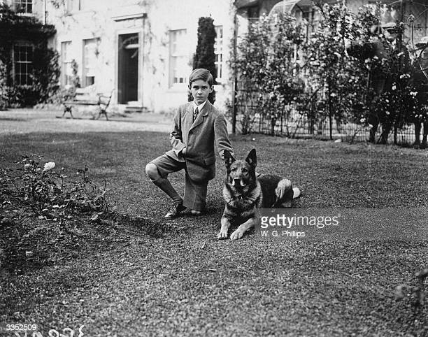 Child with an Alsatian dog lying obediently at his side.