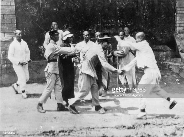 Chinese eunuchs scuffle with police following their eviction from the Forbidden City in Beijing by order of the Emperor.
