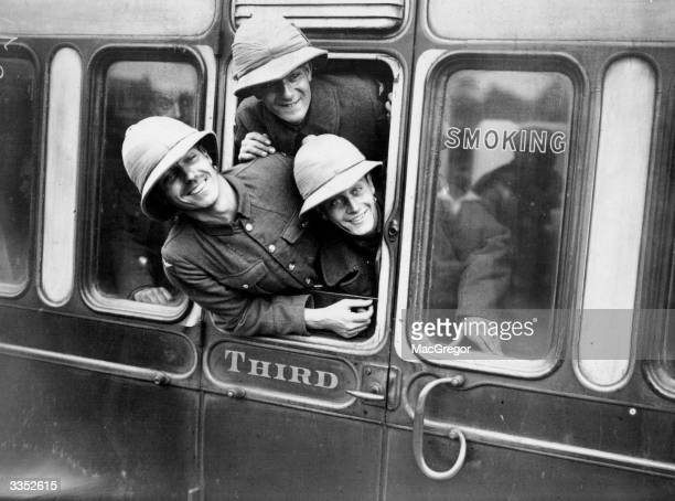 Three RAF men wearing pithhelmets peer out of a third class smoking railway carriageThey are part of draft of 1000 Officers and men leave Uxbridge...