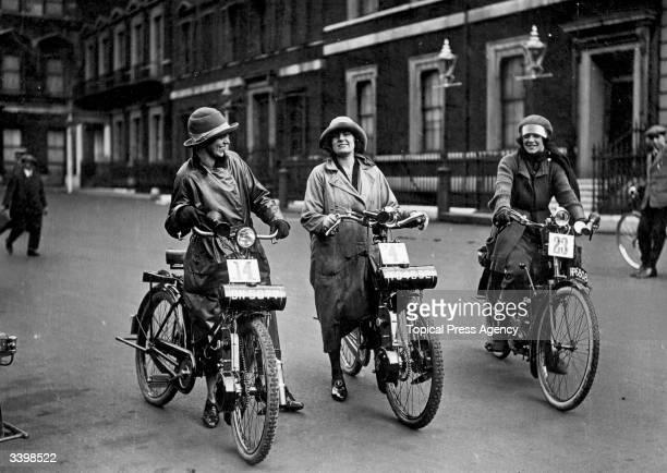 Three women waiting to start their midget motorcycle race.
