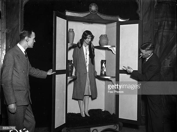 The doors of a cabinet are opened by assistants to show Miss Mary Maskelyne a woman illusionist