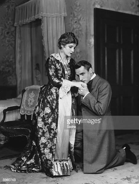 Henry Daniell kisses Fay Compton's hand on bended knee in a production of the play 'Secrets' at the Comedy Theatre