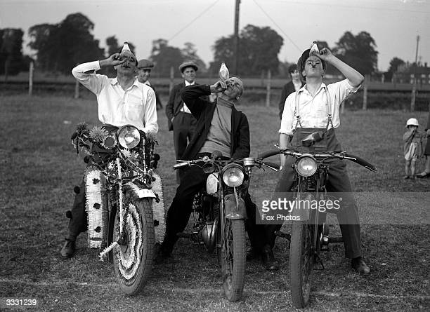 Three motorbike enthusiasts drink thirstily during a motorcycle carnival in Wokingham Surrey One of the is gaily decorated