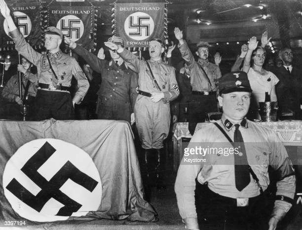 German Nazi dictator Adolf Hitler takes the salute from his followers at a meeting of the steel helmets at the Sports Palace in Berlin On his left is...