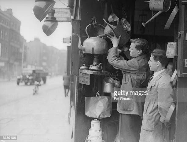 A young man fills the famous kettle in Borough which claims to boil four pints of water in five minutes