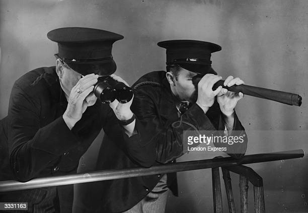 Two men pretending to be ship's crew looking out to sea A rolled up umbrella acts as a telescope while a chair back supports the 'ship's rail' This...
