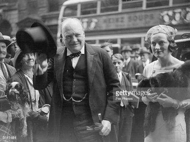 Winston Churchill raises his hat to the onlookers as he and his daughter Diana arrive for her wedding to Duncan Sandys MP