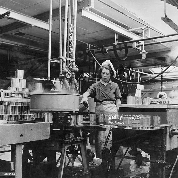 Female worker in a factory in Wisbech, Cambridgeshire, canning and preserving fruit.
