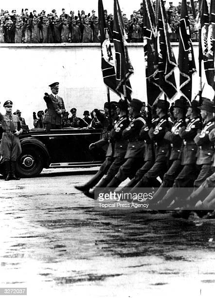 German dictator Adolf Hitler salutes as Nazi troops march past at a Nuremberg rally