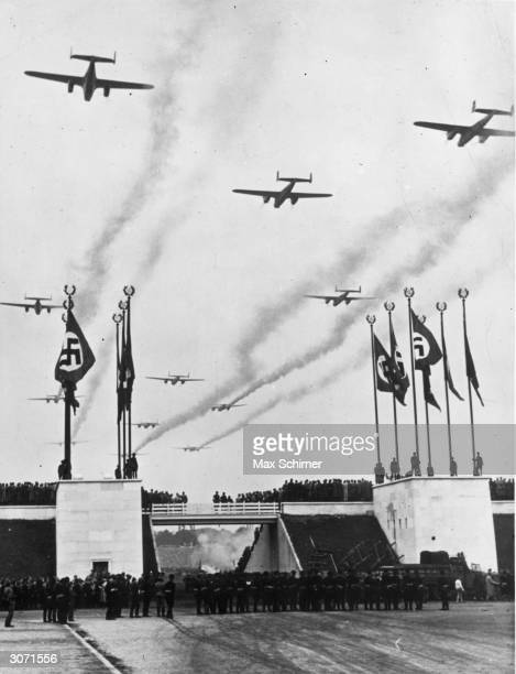 Giant bombers of the Luftwaffe leave a smoke trail as they fly over a Nuremberg rally in a show of German military might