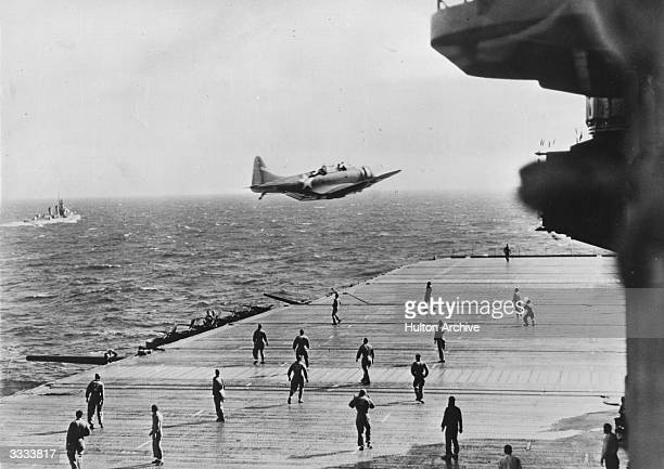 American flight deck crew of a US aircraft carrier standing by to receive a message dropped from a scouting plane on a reconnaissance flight in the...