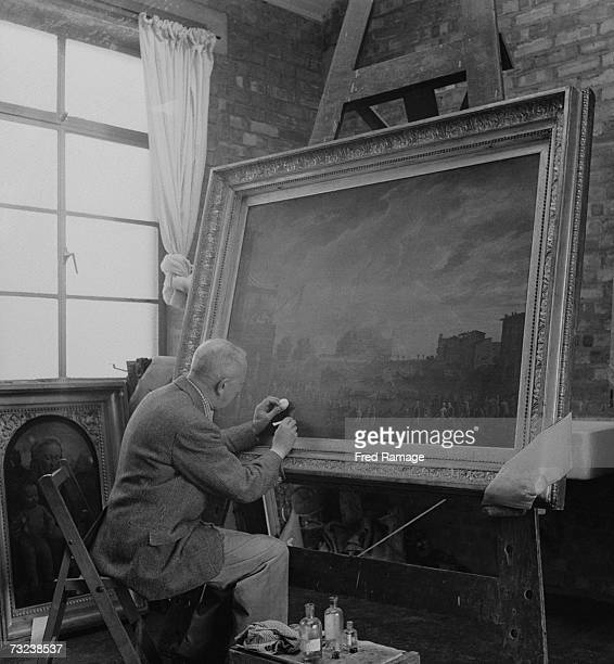 Art restorer WA Holder working on 'A Sporting Contest on the Tiber at Rome' by Joseph Vernet in a studio at Manod Quarry north Wales where paintings...