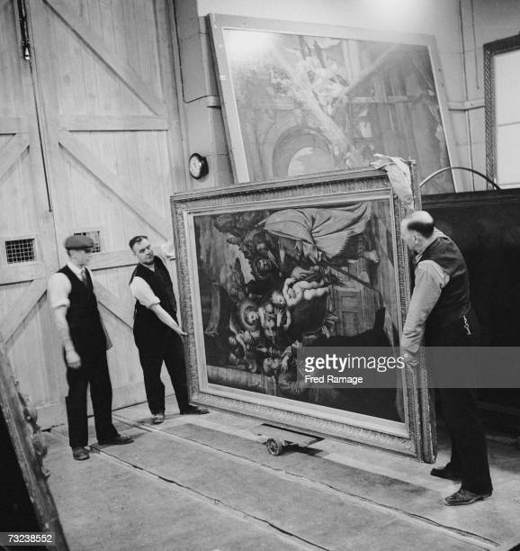 Attendants take a painting by Girolamo da Treviso out of storage for routine inspection in a subterranean chamber at Manod Quarry north Wales where...