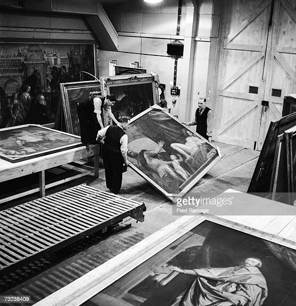 Attendants take a painting by Paolo Veronese out of storage for routine inspection in a subterranean chamber at Manod Quarry north Wales where...