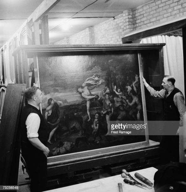 Attendants take a painting out of storage for routine inspection in a subterranean chamber at Manod Quarry north Wales where paintings from the...
