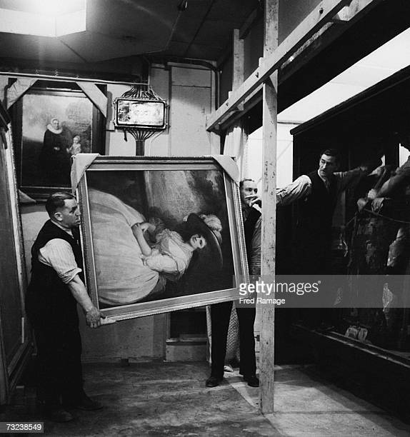 Attendants take 'Portrait of a Lady' by George Romney out of storage for restoration at an underground facility at Manod Quarry north Wales where...