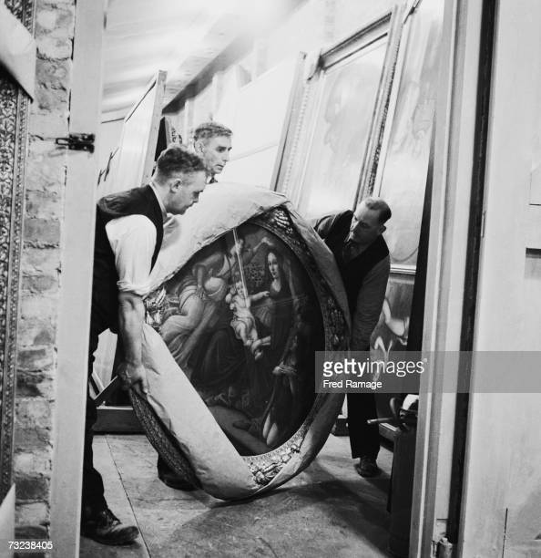 Attendants take the painting 'Mother and Child' of the Botticelli school out of storage for routine inspection in a subterranean chamber at Manod...