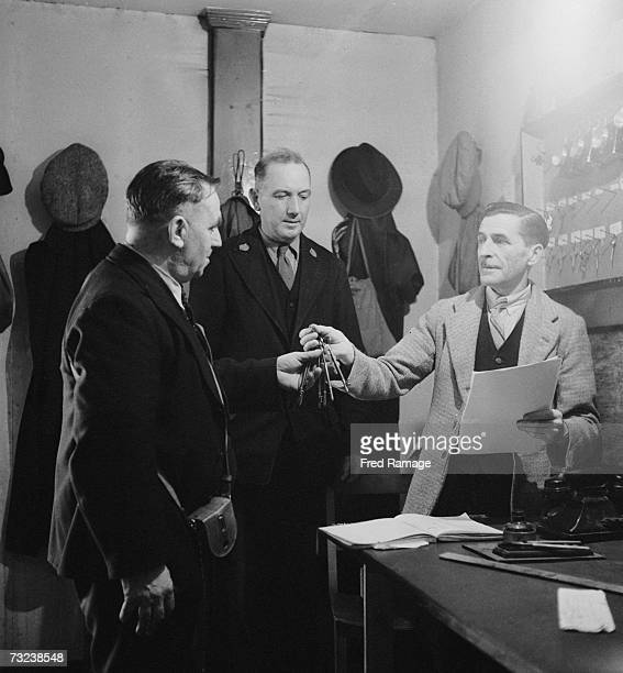 Chief Attendant EB Harrison hands a bunch of keys to colleagues at an underground facility at Manod Quarry north Wales where paintings from the...