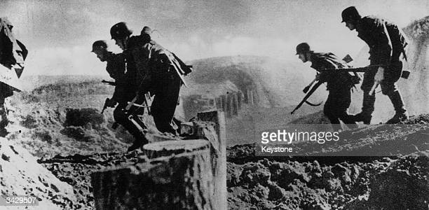 German infantry cross a semicovered tank trap in the Caucasus during WW II