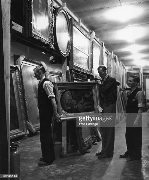 Paintings are taken out of storage and hung up in the main hall for routine inspection at an underground facility at Manod Quarry north Wales where...