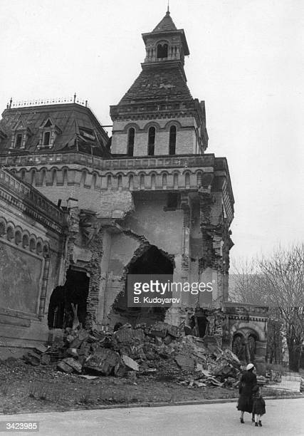 A mother and child walk past the ruins of a building in Leningrad bombed by the Nazis during the siege of the city