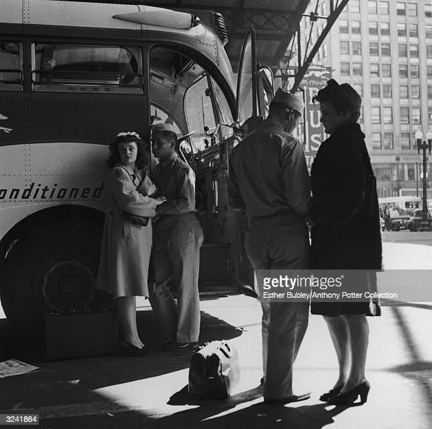 Soldiers say good-bye to their girlfriends in front of a bus at a Greyhound station in Indianapolis, Indiana, World War II.