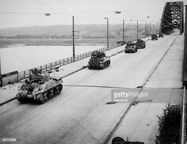Allied Sherman tanks crossing the newly-captured bridge at Nijmegen in Holland during their advance as part of 'Operation Market Garden'.
