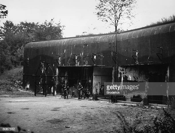 French troops outside a concrete pillbox which is the entrance to an underground fort in the Maginot line