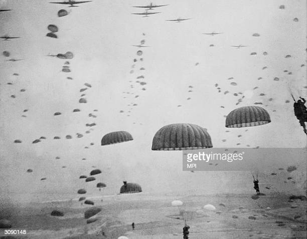 Parachutes open overhead as waves of paratroops land in Holland during operations by the 1st Allied Airbourne Army.