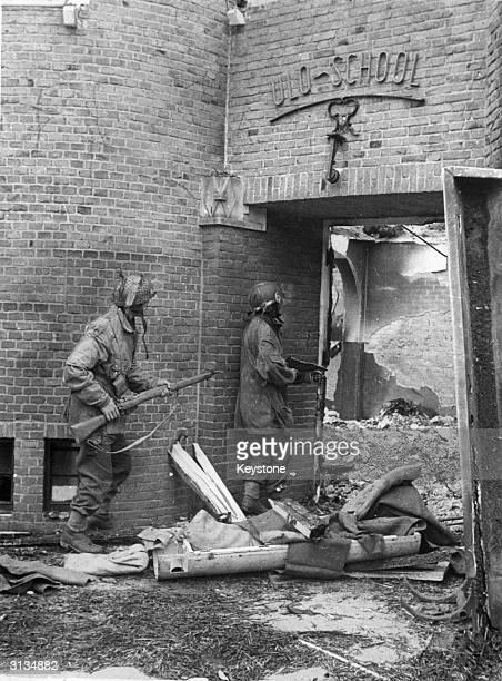Sergeants J Whawell and J Turrell of the Glider Pilot Regiment of the 1st Allied Airborne Army search a bomb damaged school in the Netherlands for...