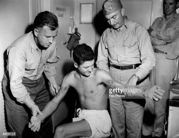 Two medical officers on the US hospital ship 'Benevolence' examine the injuries inflicted on US Army Sergeant Harold T Hedges during his internment...