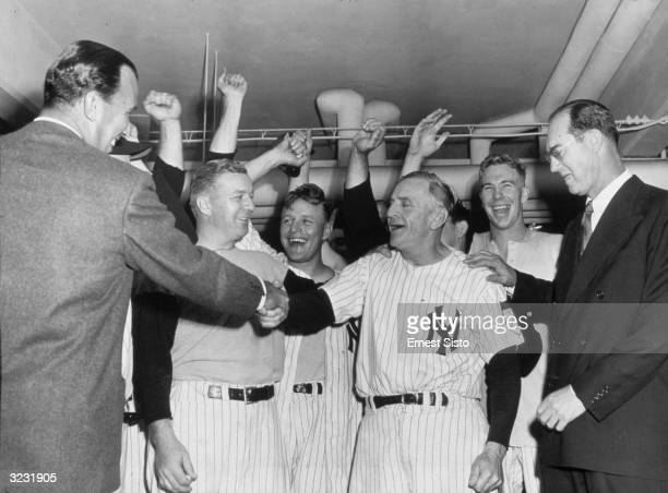New York Yankees owner Dan Topping shaking hands with Yankees manager Casey Stengel in the clubhouse after the team clinched the pennant New York...