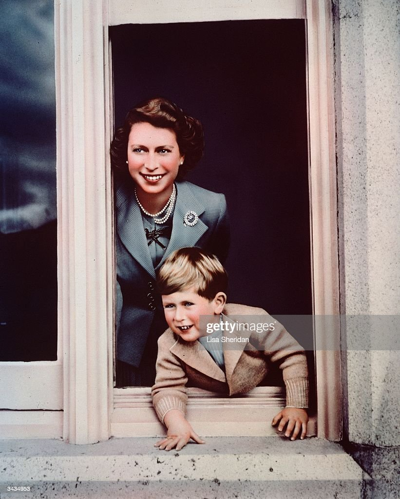 Prince Charles and his mother Princess Elizabeth looking out of a window at Balmoral.
