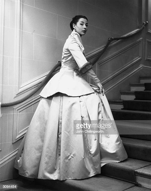 A full length evening two piece with mink cuffs by Dior The jacket flares below a tight waisted and the skirt is extremely full Original Publication...