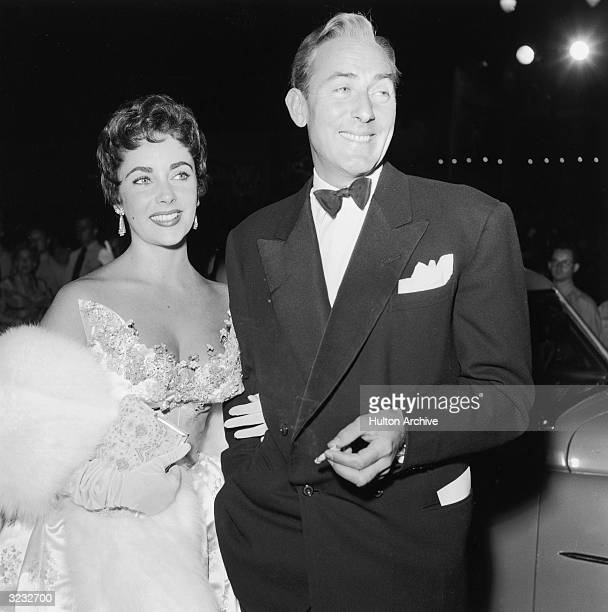 British-born actress Elizabeth Taylor with her husband, British actor Michael Wilding arrive for the premiere of director George Cukor's film 'A Star...