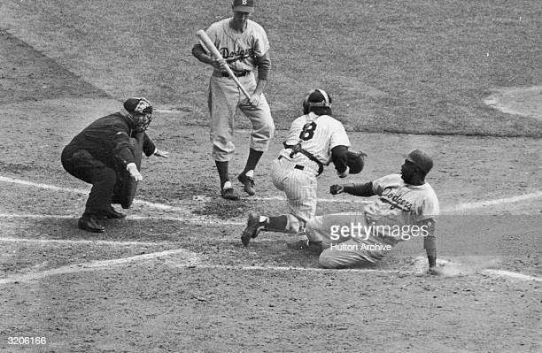 American baseball player Jackie Robinson of the Brooklyn Dodgers stealing home plate during the World Series game against the New York Yankees New...