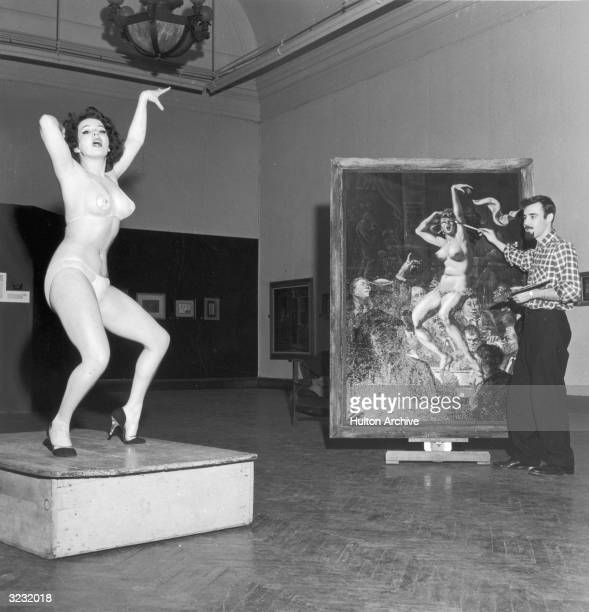 American burlesque performer Blaze Starr poses for American painter Joseph Sheppard in his studio as he finishes a 4'X6' portrait of her Starr wears...