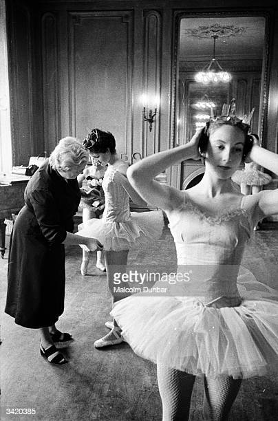 Ballet teacher Marjorie Middleton arranging a student's skirt while another student adjusts her headdress in a studio at the Scottish Ballet School...