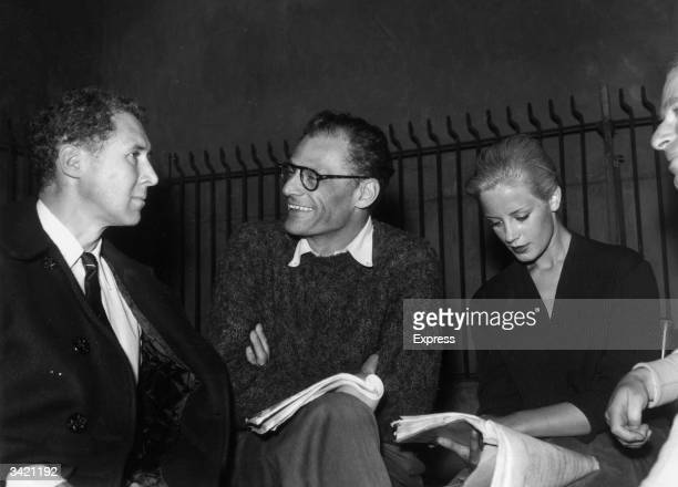 Playwright Arthur Miller talks to actor Anthony Quayle while actress Mary Ure studies a script during rehearsals of 'A View from the Bridge' at the...