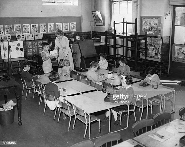 A teacher at Queen's Park Infants School Harrow Road London teaching her depleted class of 9 children usually 40 Thousands of schoolchildren have...