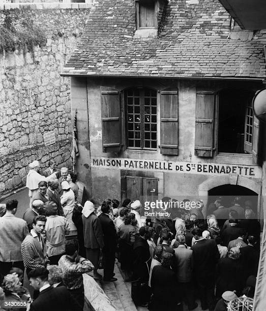Pilgrims outside the family home of St Bernadette at Lourdes France