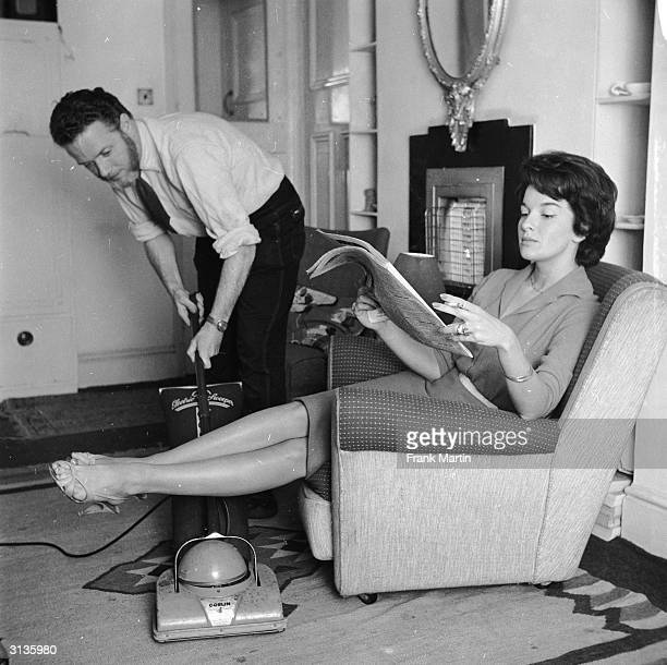 An employee of the 'Housewives Help Service' hoovering the living room of a businesswoman while she relaxes.