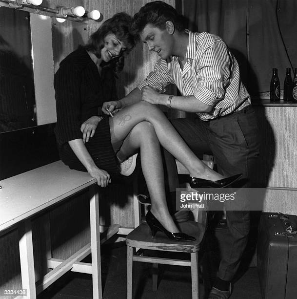English pop singer Shane Fenton, later known as Alvin Stardust, autographing a woman's leg in his dressing room.