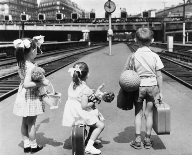 Three French children waiting on a railway platform...