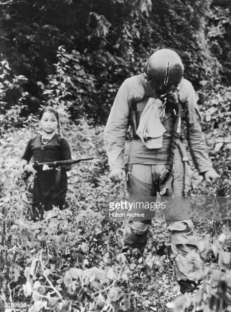 A North Vietnamese woman or girl points a rifle at American POW Gerald Santo Venanzi a first lieutenant in the US Air Force as he walks in front of...
