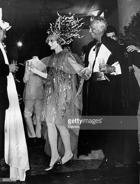 American actor Douglas Fairbanks Jr holds the hand of the Vicomtesse Jacqueline de Ribes at a masked ball in Venice Italy Fairbanks wears a...