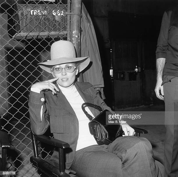 American actor Faye Dunaway seated at 'The Factory' nightclub, wearing a pants suit, a wide-brimmed felt hat, and large glasses.